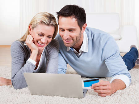 Attractive young couple lying on the floor together looking at the screen of their laptop while shopping online Stock Photo - 16885292
