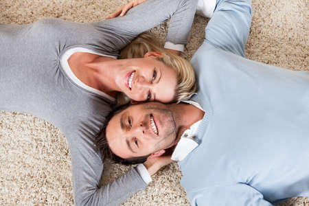 Happy relaxed attractive man and woman lying on their backs head to head on a white carpet smiling up at the camera photo