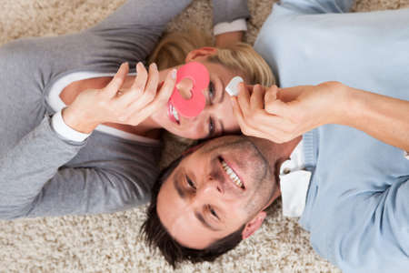 courting: Happy relaxed attractive man and woman lying on their backs head to head on a white carpet smiling up at the camera Stock Photo