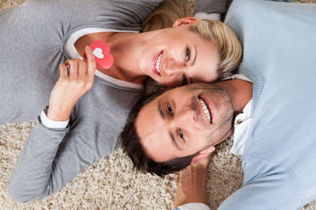 blonde couple: Happy relaxed attractive man and woman lying on their backs head to head on a white carpet smiling up at the camera Stock Photo