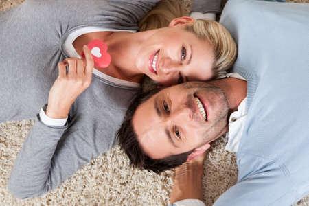 pareja en casa: Hombre feliz relajada y atractiva mujer acostada sobre su cabeza espaldas a la cabeza en una alfombra blanca sonriendo a la c�mara