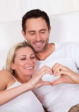 heat home: Beautiful young couple relaxing in bed at home