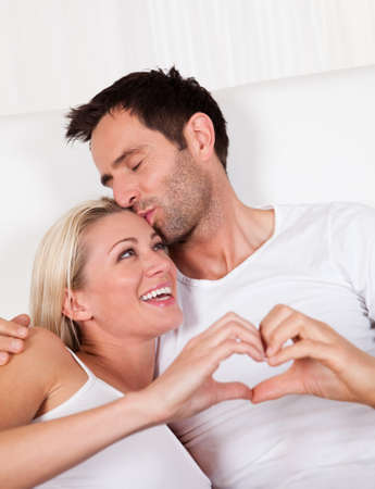 couple holding hands: Beautiful young couple relaxing in bed at home