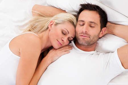 pareja durmiendo: Hermosa joven pareja se relaja en la cama en su casa Foto de archivo