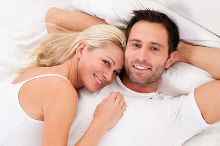 pareja en la cama: Hermosa joven pareja se relaja en la cama en su casa Foto de archivo
