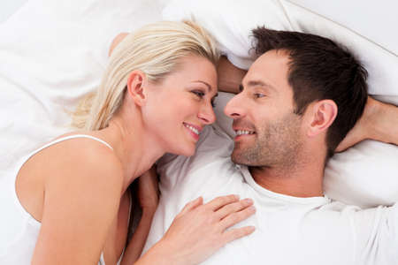 bed linen: Loving couple lying in bed gazing into each others eyes as they lie back on the pillows Stock Photo