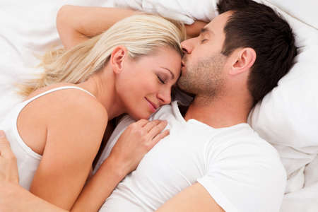 women kissing: Loving couple lying in bed gazing into each others eyes as they lie back on the pillows Stock Photo