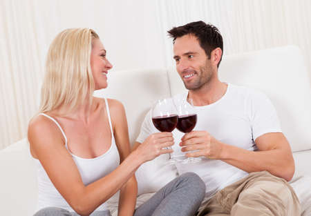 courting: Casual attractive couple relaxing at home toasting each other with large glasses of red wine Stock Photo