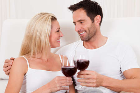 date night: Casual attractive couple relaxing at home toasting each other with large glasses of red wine Stock Photo