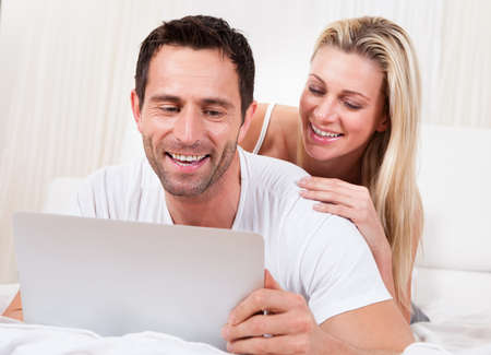 Young couple reading a laptop screen with the husband lying on his stomach on a bed and his wife leaning on him looking over his shoulder Stock Photo - 16886406