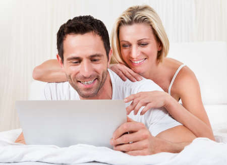 Young couple reading a laptop screen with the husband lying on his stomach on a bed and his wife leaning on him looking over his shoulder Stock Photo - 16886410