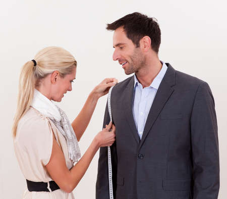 alter: Stylish blonde seamstress measuring a businessman for a suit or in order to alter the one he is wearing