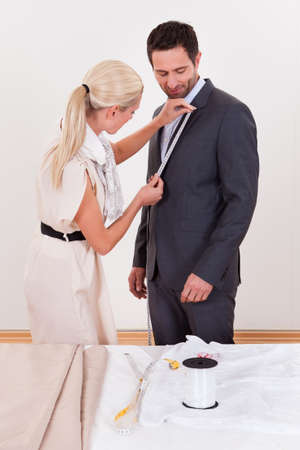 tailor measuring tape: Stylish blonde seamstress measuring a businessman for a suit or in order to alter the one he is wearing