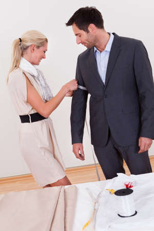 Stylish blonde seamstress measuring a businessman for a suit or in order to alter the one he is wearing photo