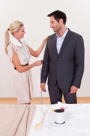 Elegante sarta bionda misurazione di un uomo d'affari per un vestito o per alterare quella che indossa Archivio Fotografico