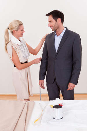 tailor measure: Stylish blonde seamstress measuring a businessman for a suit or in order to alter the one he is wearing