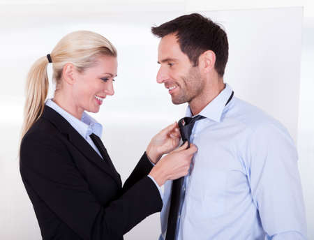 adjust: Businesswoman putting tie on businessman in the office Stock Photo