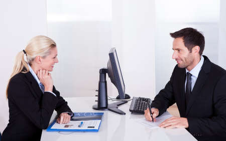 A male and female business partner having a meeting sitting on either side of a table taking notes and discussing the contents of a folder photo