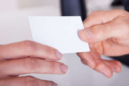 businesswoman card: Closeup cropped view image of a man handing a woman a blank white business card for your advertising or contact details Stock Photo