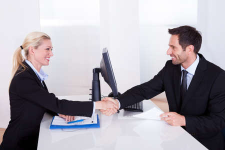 business partner: Business man and woman shaking hands over the top of a desk as they clinch a deal