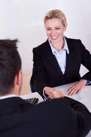 hire: A female business executive smiling at her male colleague.