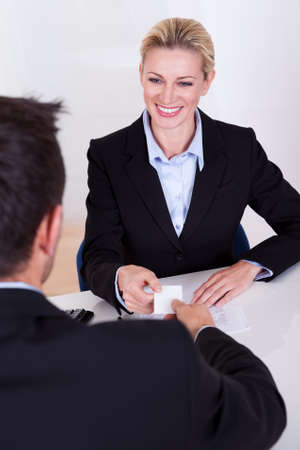 exchanging: A female business executive smiling at her male colleague.