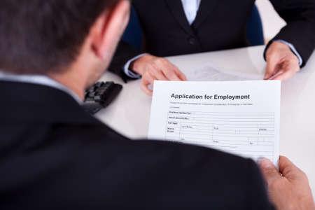 entrevista: Empresario la realizaci�n de una entrevista de trabajo con un hombro sobre la vista de un formulario de solicitud