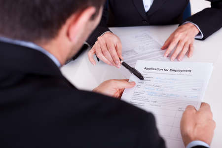 curriculum: Businessman conducting an employment interview with an over the shoulder view of an application form Stock Photo