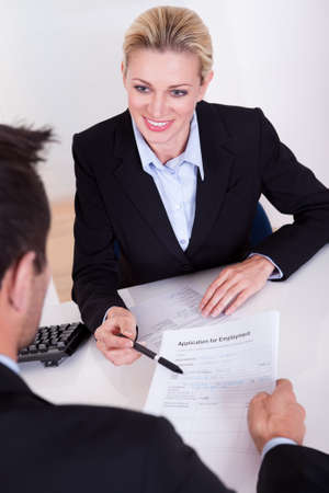 vitae: Businessman conducting an employment interview with an over the shoulder view of an application form Stock Photo