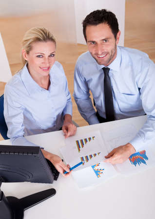 Smiling business colleagues sitting behind a desk discussing statistics with bar graphs in their hands photo