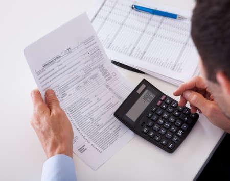 Over de schouder van een man controle een factuur calculator