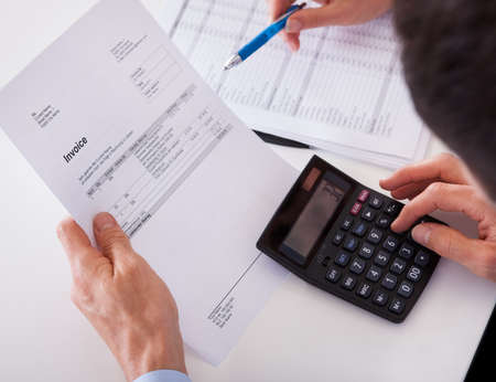 economia aziendale: Da sopra le spalle di un uomo di controllo una fattura su una calcolatrice Archivio Fotografico