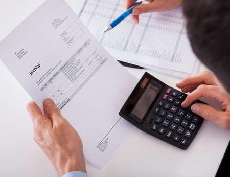 administracion de empresas: Vista por la espalda de un hombre de comprobar una factura en una calculadora Foto de archivo