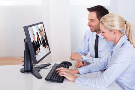 Professional couple sitting together at a desk watching an online presentation on the computer monitor photo