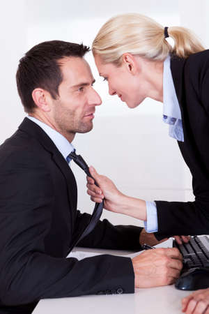 seducing: Flirting in the office as a beautiful blonde businesswoman pulls a colleague towards her by his tie