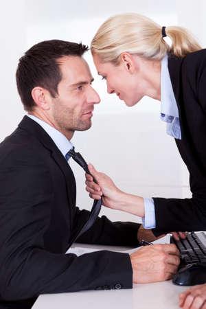 acoso laboral: Me encanta coquetear en la oficina como una mujer de negocios hermosa rubia saca un colega hacia ella por la corbata
