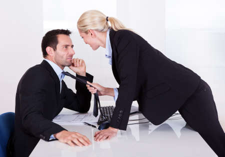 Flirting in the office as a beautiful blonde businesswoman pulls a colleague towards her by his tie photo