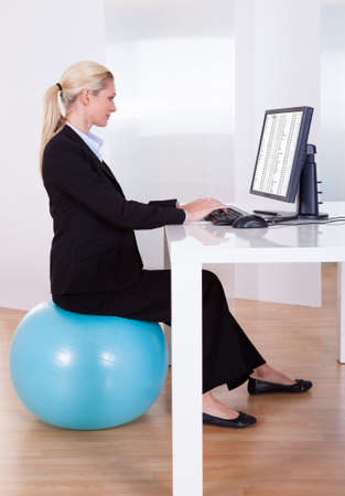 position: Comfortable working environment with an elegant young blonde office worker sitting on a pilates ball