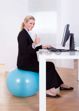workplace wellness: Comfortable working environment with an elegant young blonde office worker sitting on a pilates ball