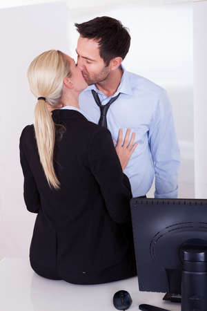 A businessman embraces a female colleague who is sitting on a desktop as mutual passion leads to an affair or love in the workplace photo