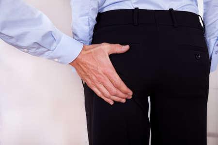 acoso laboral: Imagen conceptual del acoso en el lugar de trabajo con un hombre que estira la mano para tocar un fondo colegas