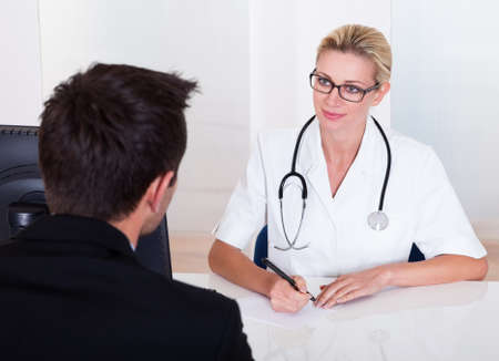 Attractive female doctor wearing glasses and a stethoscope consulting with a male patient with his back to the camera Stock Photo - 16874363