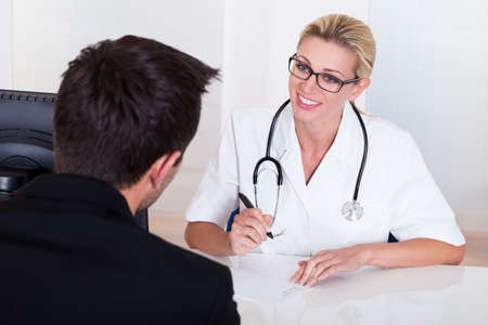 Attractive female doctor wearing glasses and a stethoscope consulting with a male patient with his back to the camera Stock Photo - 16874263
