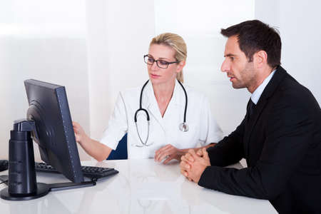 Attractive female doctor sitting at her desk pointing to a computer screen explaining something to a male patient Stock Photo - 16874326