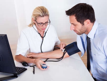 hypotension: Attractive young female doctor or nurse taking a male patients blood pressure using a sphygmomanometer
