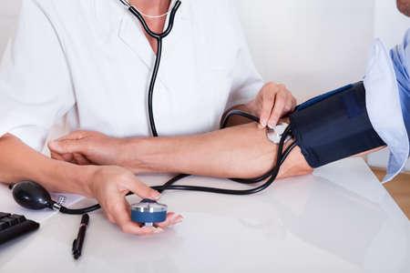 hipertension: Atractivo joven doctora o enfermera toma la presión arterial pacientes masculinos con un esfigmomanómetro