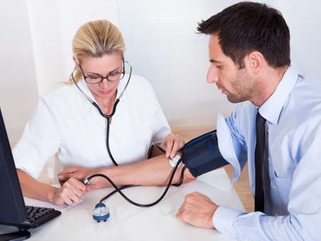pressure: Attractive young female doctor or nurse taking a male patients blood pressure using a sphygmomanometer