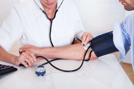nursing treatment: Atractivo joven doctora o enfermera toma la presi�n arterial pacientes masculinos con un esfigmoman�metro