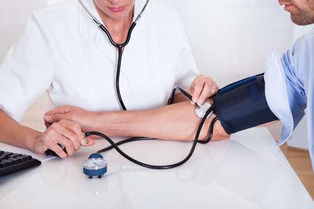 Attrayante jeune femme médecin ou une infirmière prend la tension artérielle des patients masculins avec un sphygmomanomètre
