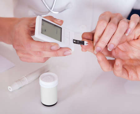 blood sugar: Doctor testing a patients glucose level after pricking his finger to draw a drop of blood and then using a digital glucometer